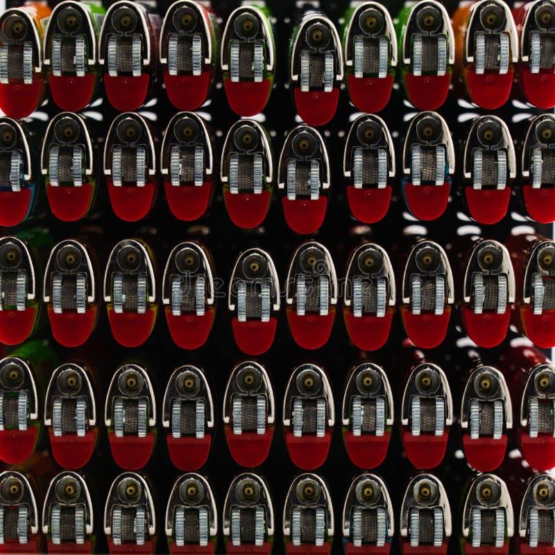 Muitos isqueiros de cor permanecem em linha isolados em fundo branco fotografia de stock royalty free