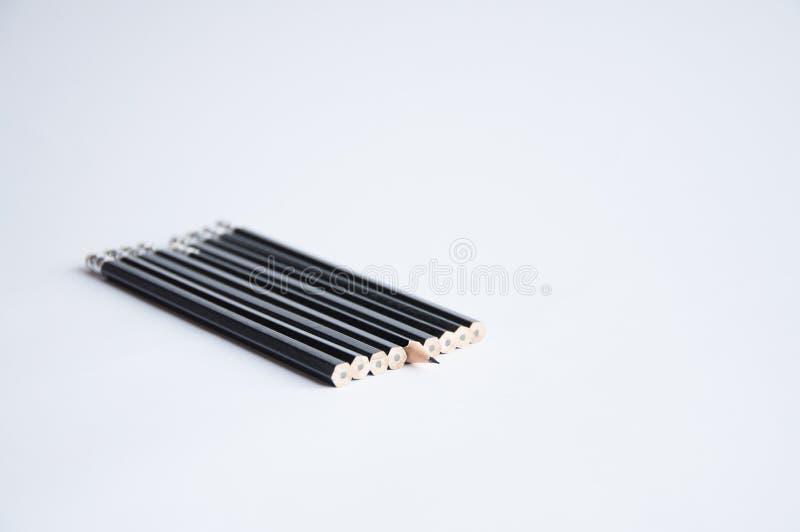 Muitos lápis pretos estão na tabela branca Um lápis apontou imagens de stock
