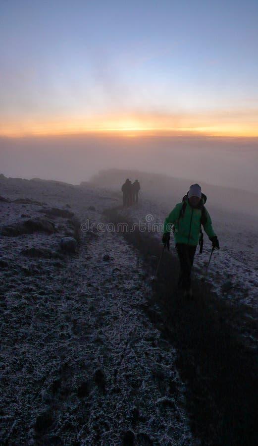 Muitos montanhistas e guias da montanha chegam na cimeira do Monte Kilimanjaro imediatamente depois do nascer do sol imagem de stock