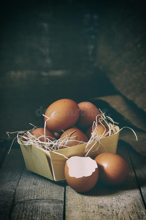 Muitos ovos da vila encontram-se em uma cesta de vime na capoeira de galinha no assoalho de madeira imagens de stock royalty free