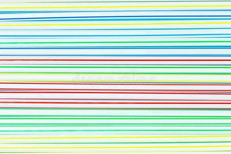 Muitos palhas ou tubos plásticos coloridos com as listras azuis, vermelhas, amarelas e verdes abstraia o fundo imagens de stock royalty free
