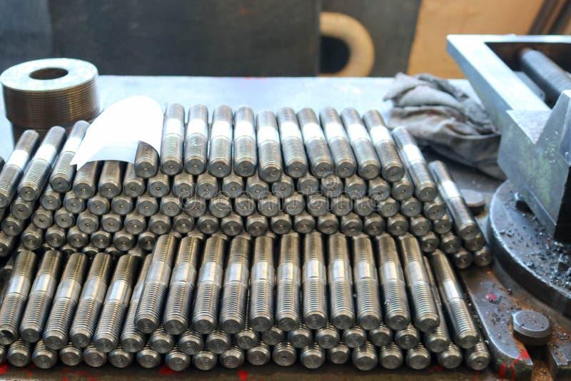 Muitos parafusos prisioneiros brilhantes do metal com cinzeladura, porcas, anéis do ferro, gaxetas, ferramentas do trabajo em met imagem de stock