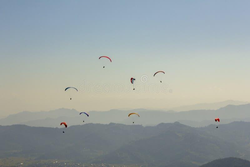 Muitos paragliders em paraquedas coloridos brilhantes voam acima de uma opinião aérea do vale da montanha enevoada fotos de stock