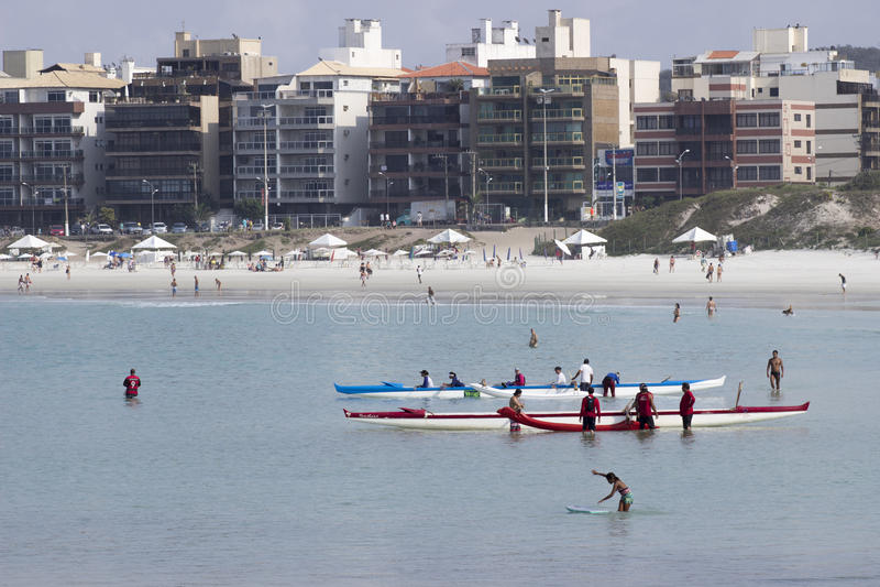Muitos povos que praticam a canoa havaiana na praia foto de stock