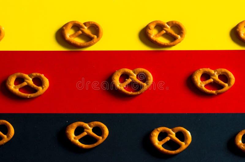 Muitos pretzeis pequenos em um fundo das cores alemãs da bandeira fotos de stock royalty free