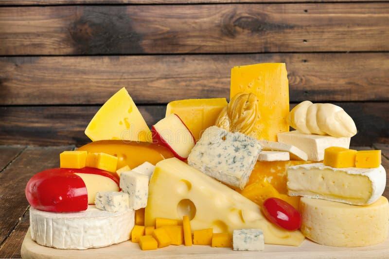 Muitos queijos envelhecidos deliciosos na placa de madeira foto de stock