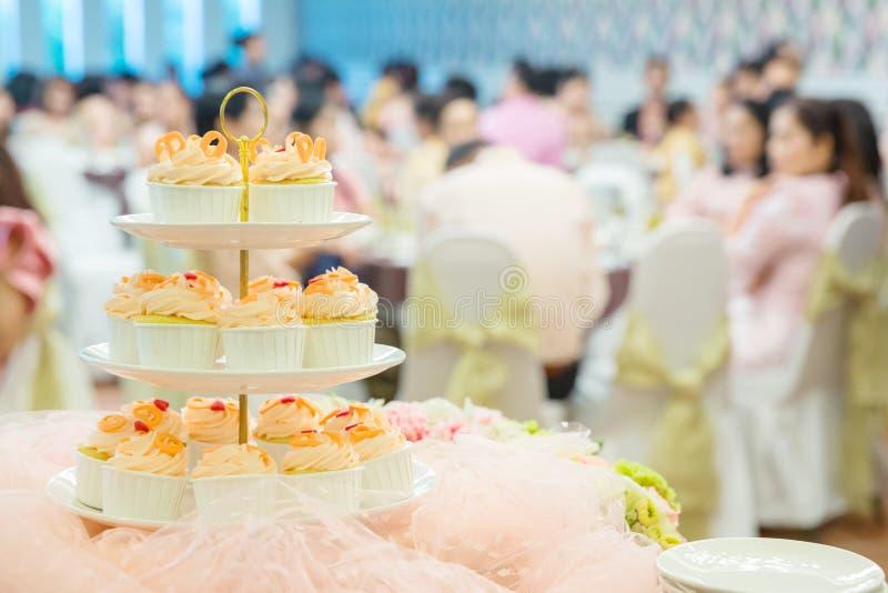muitos queques em prateleiras da prateleira no banquete de casamento serviço da sobremesa para bolos dos doces do convidado do ca imagem de stock royalty free