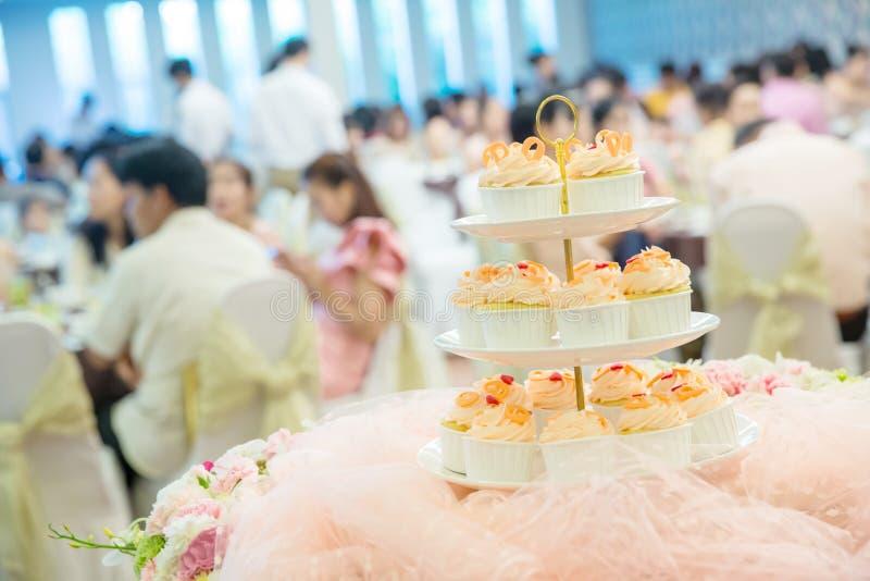 muitos queques em prateleiras da prateleira no banquete de casamento serviço da sobremesa para bolos dos doces do convidado do ca imagem de stock