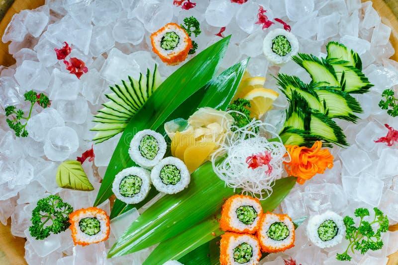 Muitos rolos de sushi com enchimentos diferentes O tiro do alimento japonês clássico cozinhado serviu no gelo Imagem de fundo imagem de stock