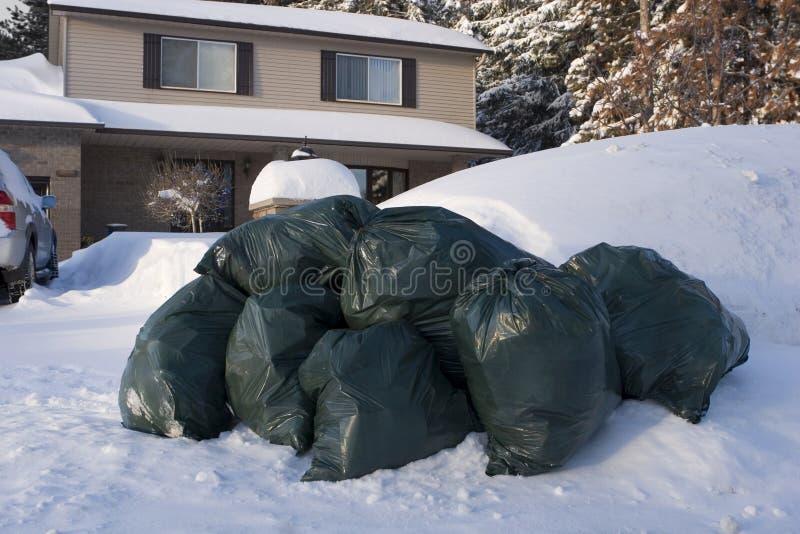 Muitos sacos de lixo verdes no inverno do freio nevam foto de stock
