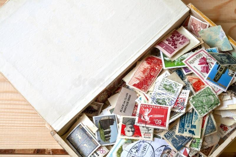 Muitos selos postais coloridos velhos de países diferentes na caixa velha que encontra-se em um fundo de madeira fotografia de stock