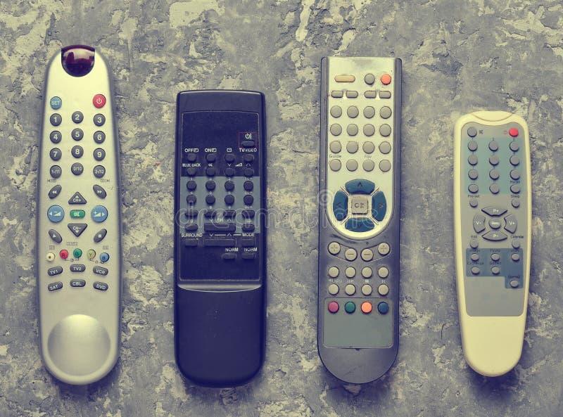 Muitos telecontroles da tevê em uma tabela concreta cinzenta Vista superior foto de stock