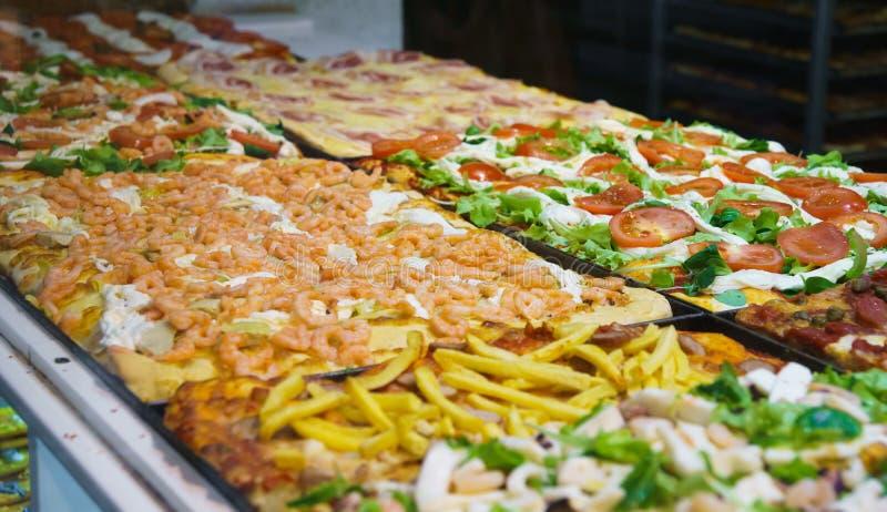 Muitos tipos de pizza italiana verdadeira em todas as variedades na pizaria italiana real imagens de stock