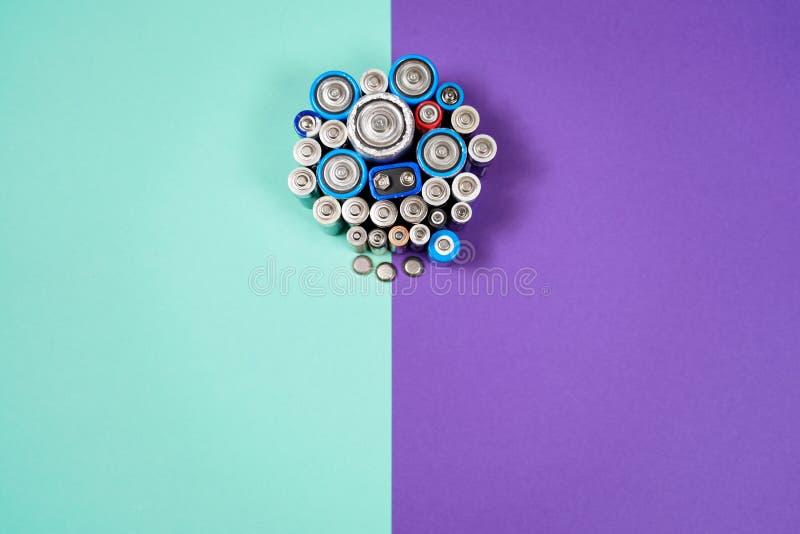 Muitos tipos diferentes usados ou bateria nova, acumulador recarregável, pilhas alcalinas no fundo da cor imagens de stock