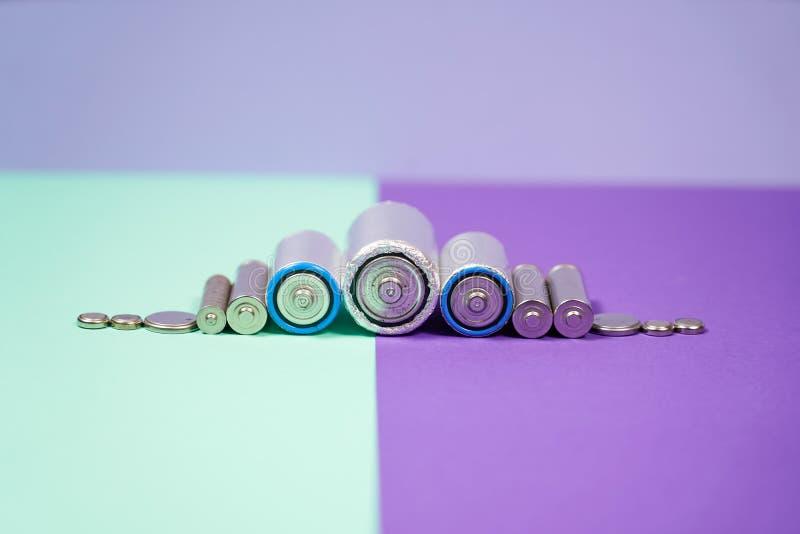 Muitos tipos diferentes usados ou bateria nova, acumulador recarregável, pilhas alcalinas no fundo da cor fotos de stock royalty free