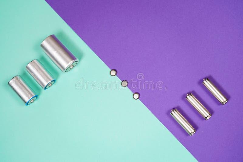 Muitos tipos diferentes usados ou bateria nova, acumulador recarregável, pilhas alcalinas no fundo da cor imagem de stock