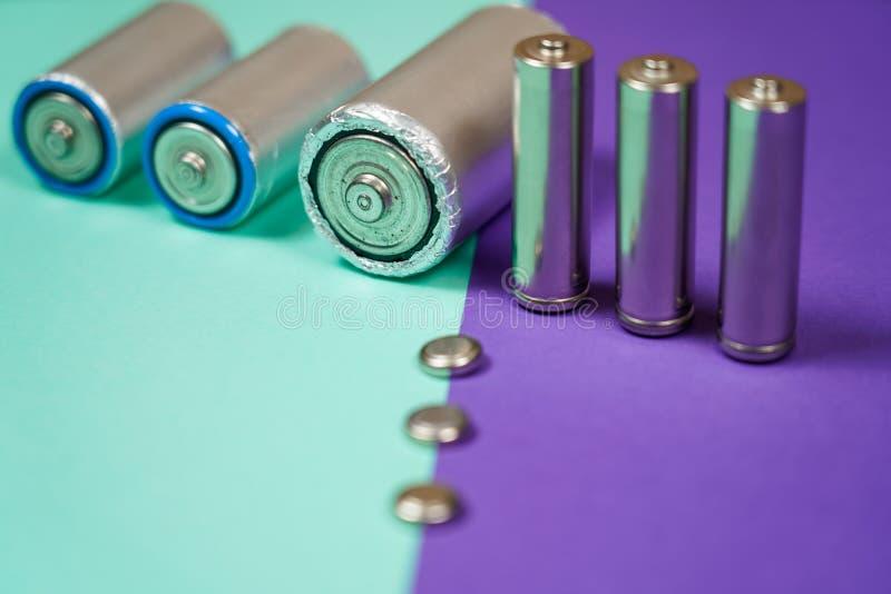 Muitos tipos diferentes usados ou bateria nova, acumulador recarreg?vel, pilhas alcalinas no fundo da cor imagem de stock