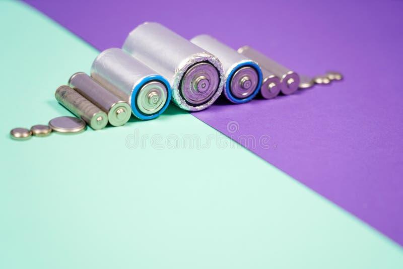Muitos tipos diferentes usados ou bateria nova, acumulador recarreg?vel, pilhas alcalinas no fundo da cor imagem de stock royalty free