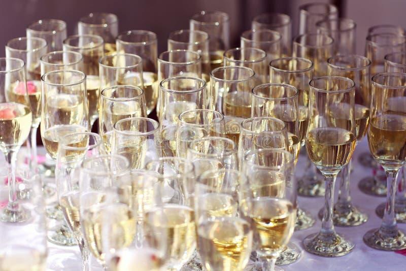 Muitos vidros do vinho no evento do casamento da tabela ou do champanhe imagens de stock