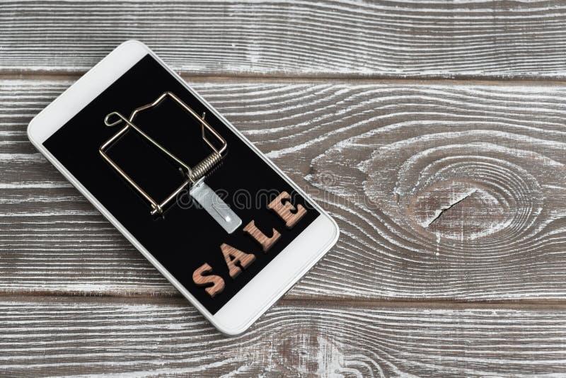Muizeval, smartphone, korting op de achtergrond van een houten lijst stock afbeeldingen