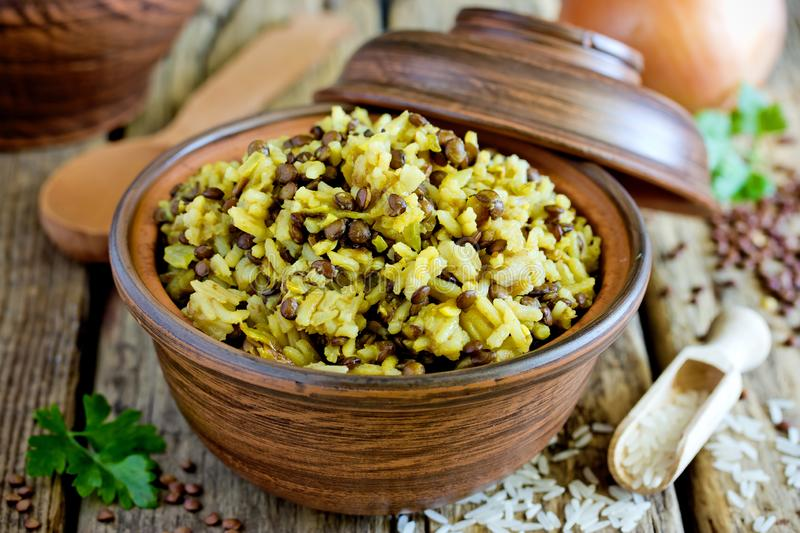 Mujadara - lentils and rice pilaf, middle eastern cuisine recipe. Mujadara - lentils and rice pilaf with caramelized onion on wooden background, middle eastern stock photography