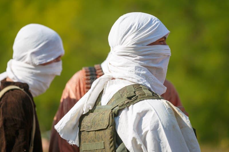 Mujahideen tre i vit kläder på bakgrunden av grön lövverk arkivfoton