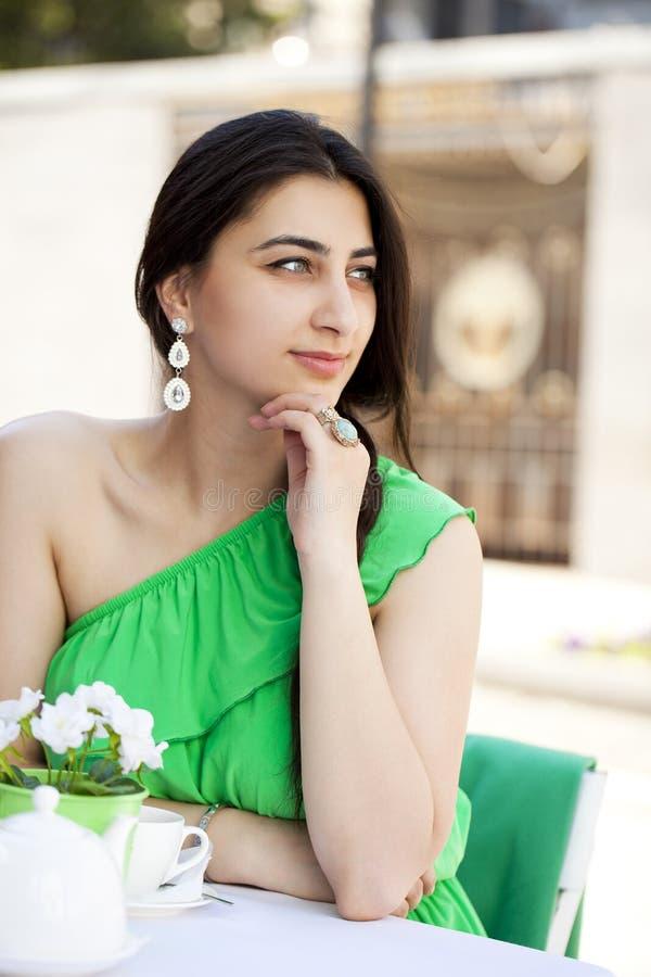 Mujer árabe bastante joven que se sienta en el café fotos de archivo