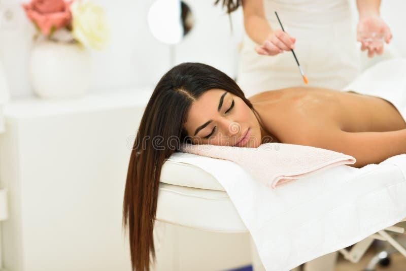 Mujer árabe en el balneario de la belleza de la salud que tiene masaje de la terapia del aroma fotografía de archivo libre de regalías