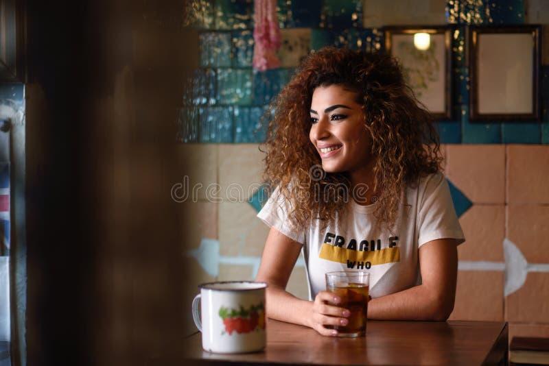 Mujer árabe en una barra hermosa que mira a través de la ventana imagen de archivo