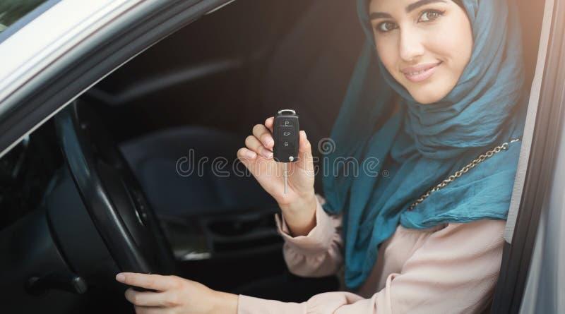 Mujer árabe feliz que lleva a cabo llave del coche en nuevo vehículo imagen de archivo