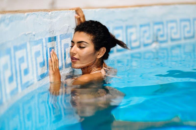 Mujer árabe hermosa que se relaja en piscina foto de archivo