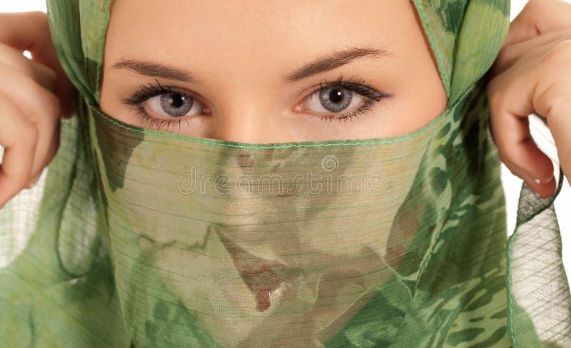 Mujer árabe joven con el velo que muestra los ojos aislados fotos de archivo