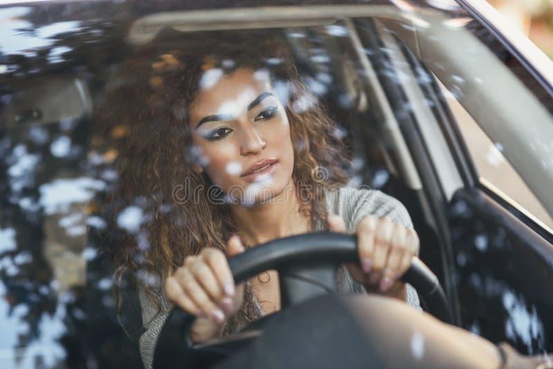 Mujer árabe joven dentro de un coche blanco que mira a través de la ventana imagen de archivo libre de regalías