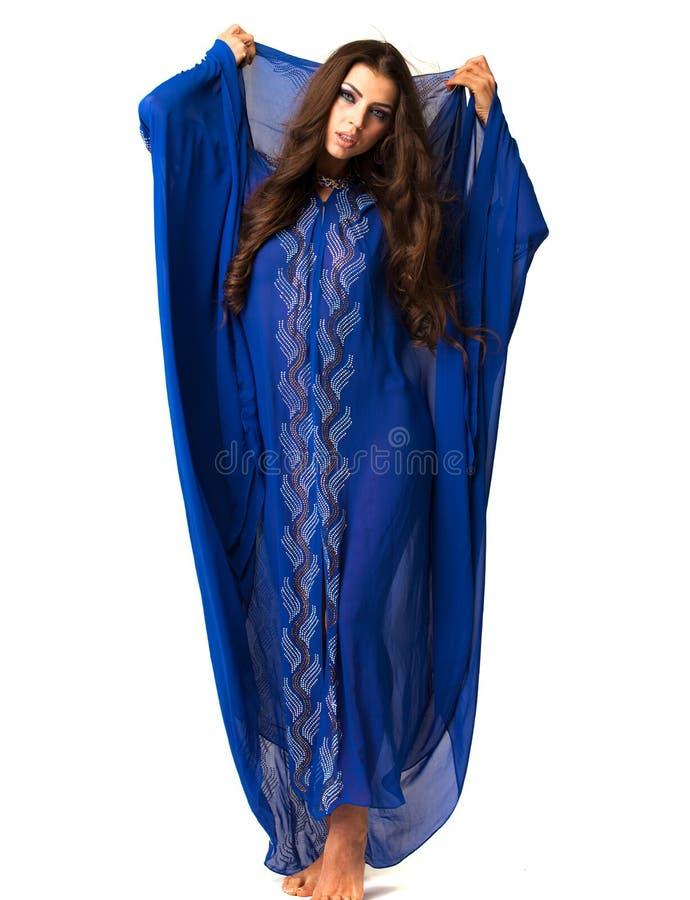 Mujer árabe joven en vestido azul largo fotografía de archivo