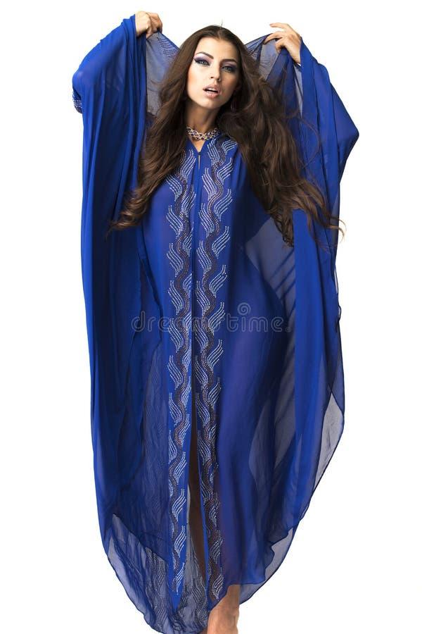Mujer árabe joven en vestido azul largo foto de archivo libre de regalías
