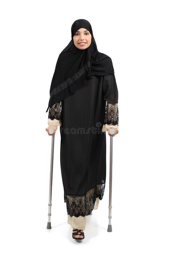 Mujer árabe que camina con las muletas imagen de archivo