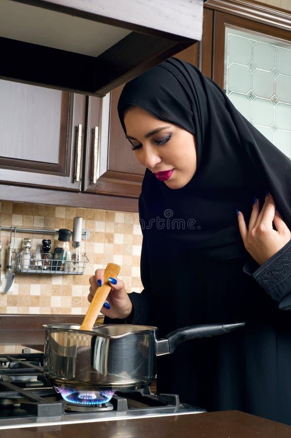 Mujer árabe que cocina el guisado en la cocina foto de archivo libre de regalías