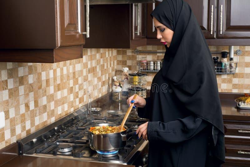 Mujer árabe que cocina el guisado en la cocina fotos de archivo libres de regalías