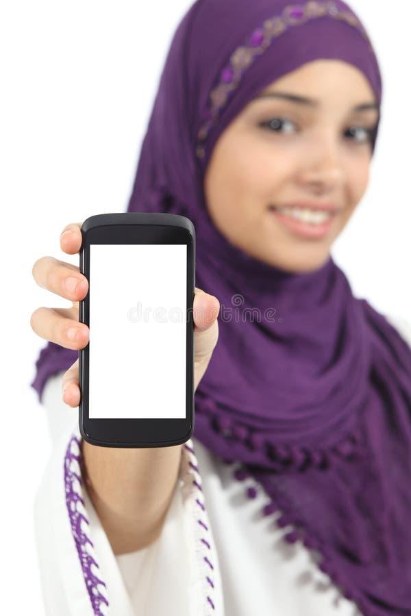 Mujer árabe que exhibe una pantalla elegante en blanco del teléfono del app imagen de archivo libre de regalías