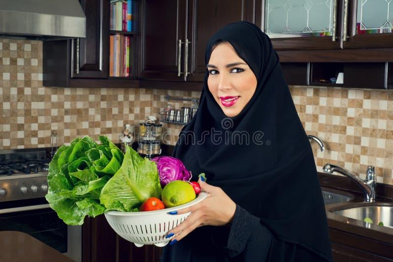 Mujer árabe que lleva sosteniendo un cuenco de veggies en la cocina foto de archivo