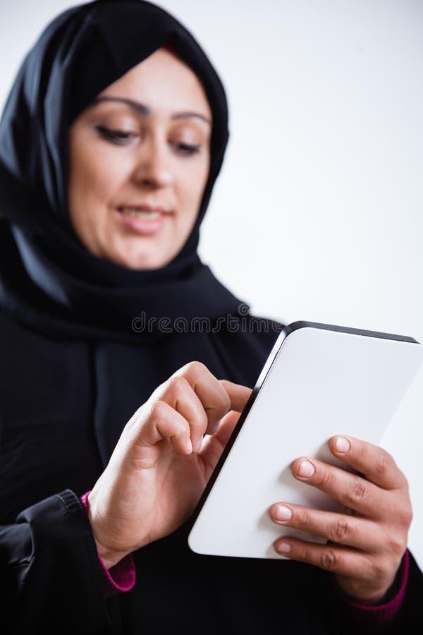 Mujer árabe que usa la tableta digital foto de archivo libre de regalías