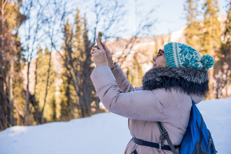 Mujer 50 años que toman la foto en las montañas en invierno, Alma foto de archivo