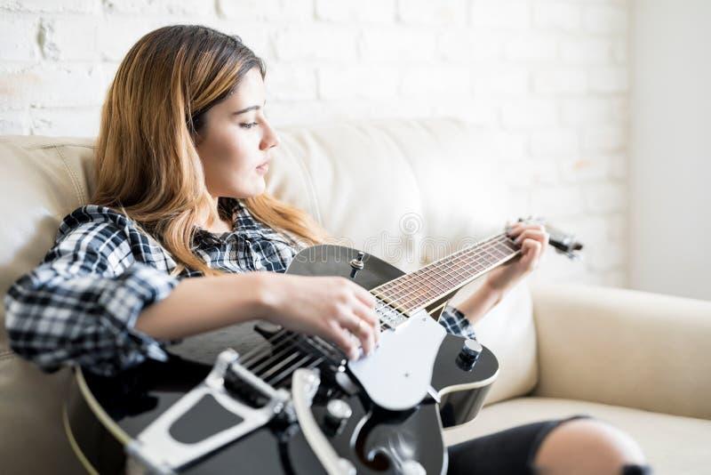 Mujer absorbida en tocar la guitarra imagenes de archivo