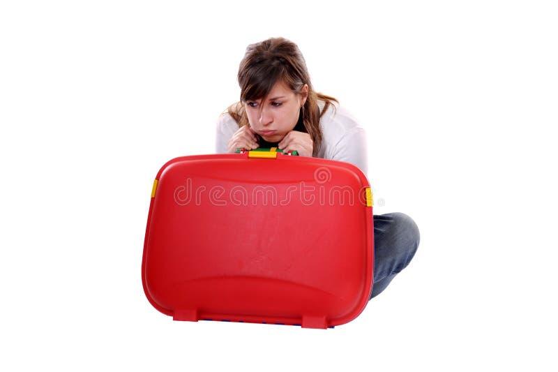 Mujer aburrida joven del concepto del recorrido con la maleta fotografía de archivo