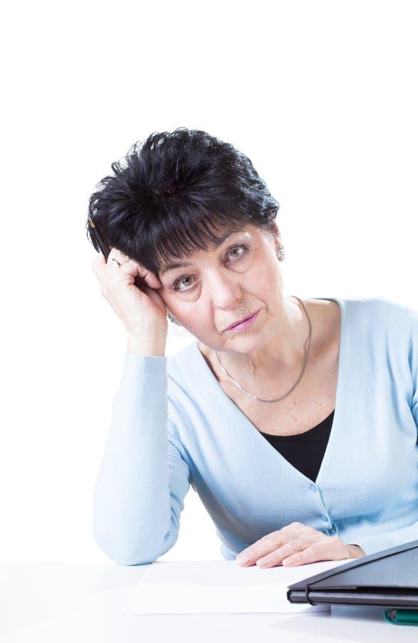Mujer aburrida y cansada en el trabajo imagen de archivo