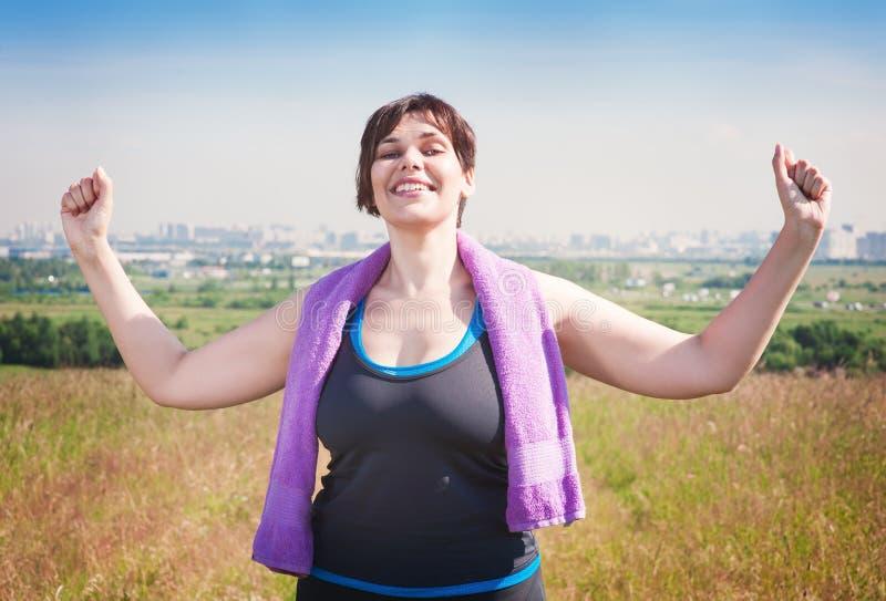 Mujer acertada feliz del tamaño extra grande que aumenta los brazos al cielo fotografía de archivo libre de regalías