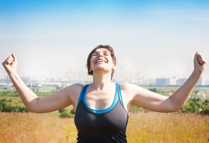 Mujer acertada hermosa feliz del tamaño extra grande que aumenta los brazos al s fotos de archivo