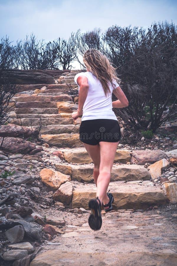 Mujer activa apta que funciona con para arriba las escaleras en paisaje al aire libre imagen de archivo