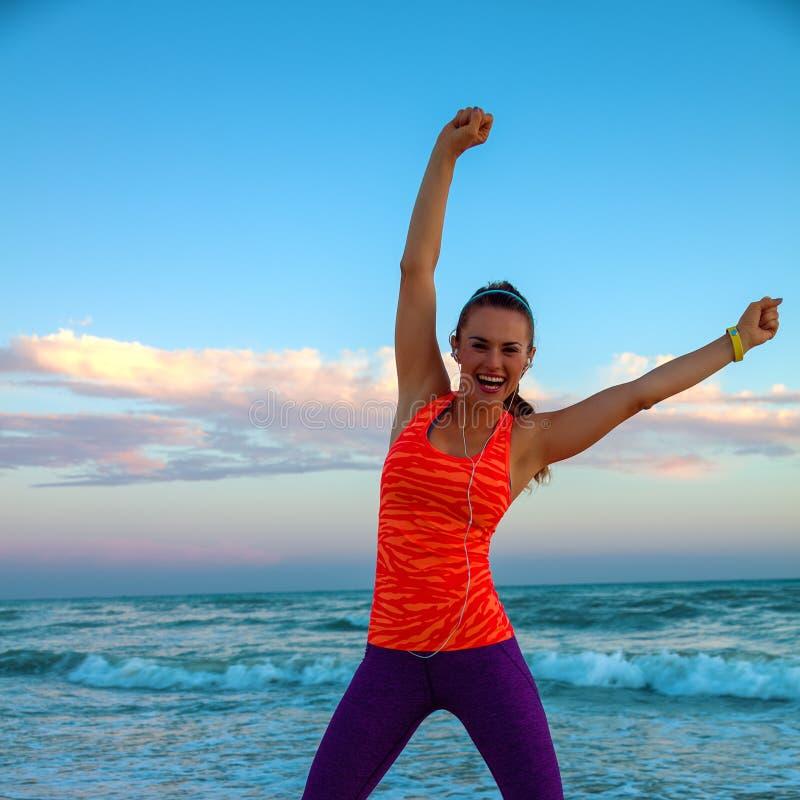 Mujer activa feliz en la costa en el júbilo de la puesta del sol foto de archivo