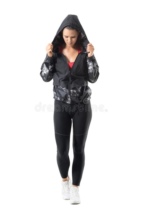 Mujer activa joven resuelta que sostiene el cuello de la sudadera con capucha que mira abajo de conseguir listo para correr imagen de archivo libre de regalías
